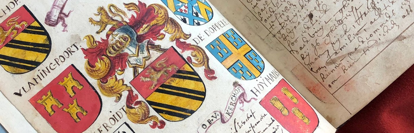Photo of an open manuscript, with colorful images of crests on one page and writing on the other